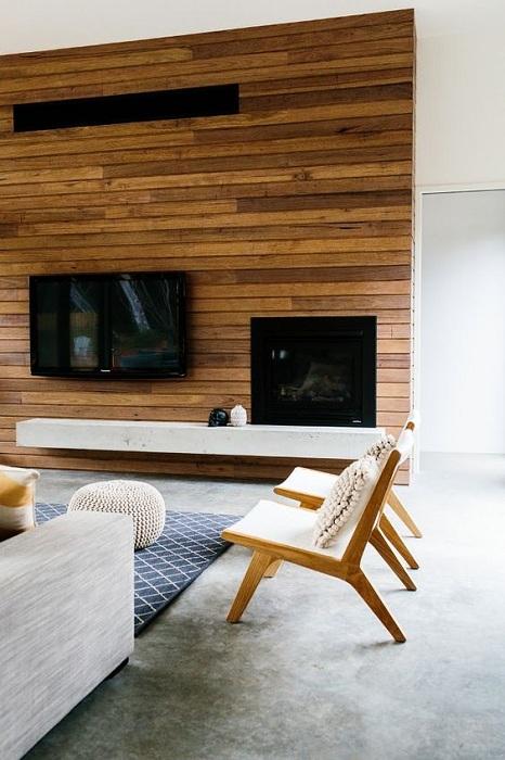 Симпатичный интерьер гостиной приукрашен при помощи просто невероятной стены выполненной из дерева.