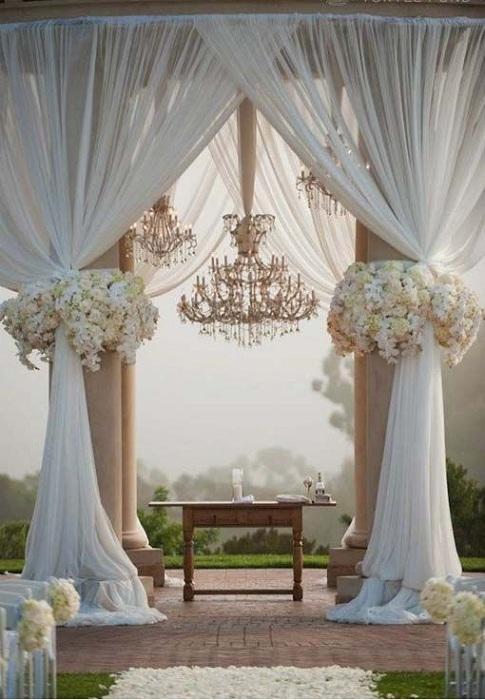 Прекрасное оформление свадебной беседки с белоснежными шторами, украшена цветами.