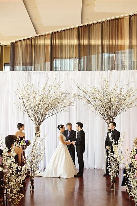 Креативное решение использования цветущих деревьев и веток при оформлении свадебного пиршества.