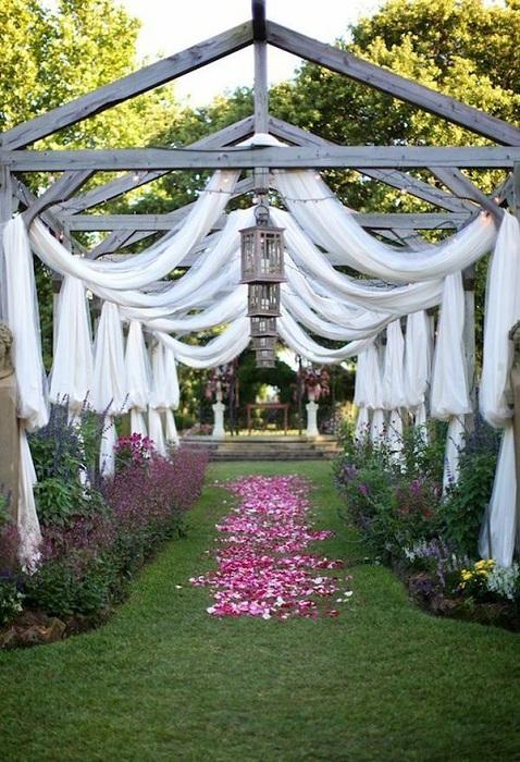 Милая свадебная беседка с белыми шторами, которые хорошо впишутся в свадебную атмосферу.