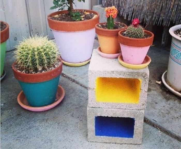 Отличный вариант создать из шлакоблоков интересные яркие варианты в виде подставок для цветов.