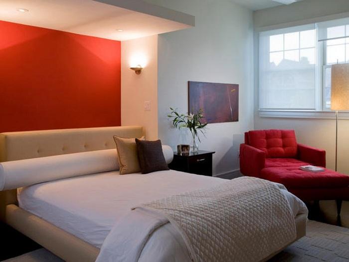 Стена окрашена в красный цвет, что преображает комнату.