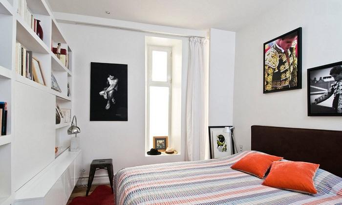 Контрастное сочетание белых поверхностей с темными оттенками изголовья кровати и рамок для фото.