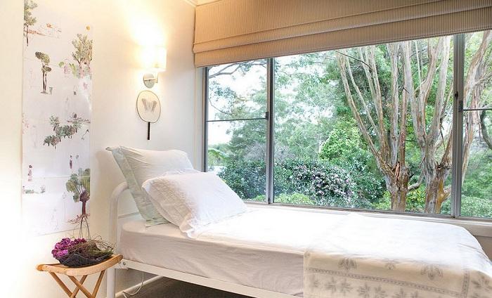 Небольшая светлый спальня делает легкий реверанс восточному стилю в интерьере.