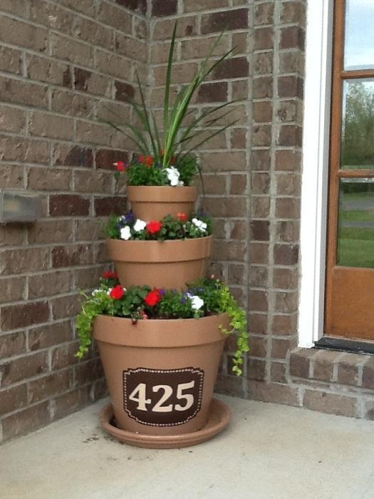 Разместить номер дома возможно на обычных и интересных горшках, что создадут домашнюю и уютную обстановку.