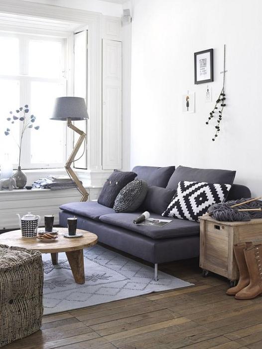 Креативное решение обустроить гостиную в оригинальной цветовой гамме с крутым темно-синим диваном.