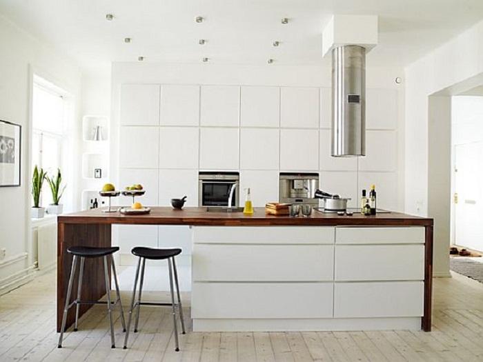 Отличный вариант размещения стола в центре кухни, что станет самым лучшим решением для декора такого плана комнаты.