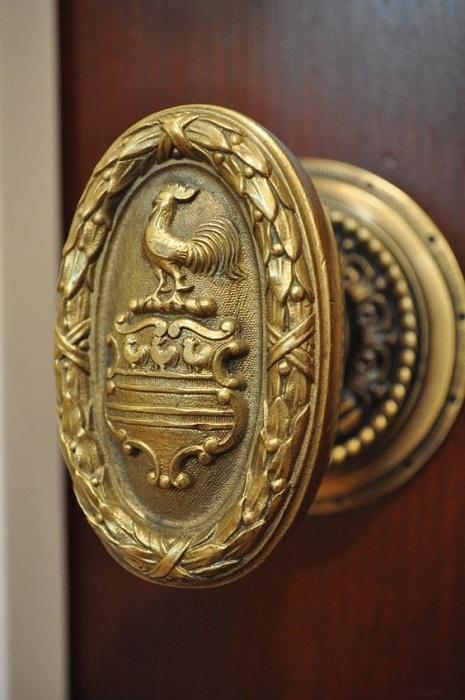 Интересная дверная ручка с изображением петушка оформлена в золотом цвете.