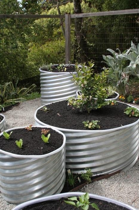 Поднятый сад при помощи обустройства его разрезанными трубами.