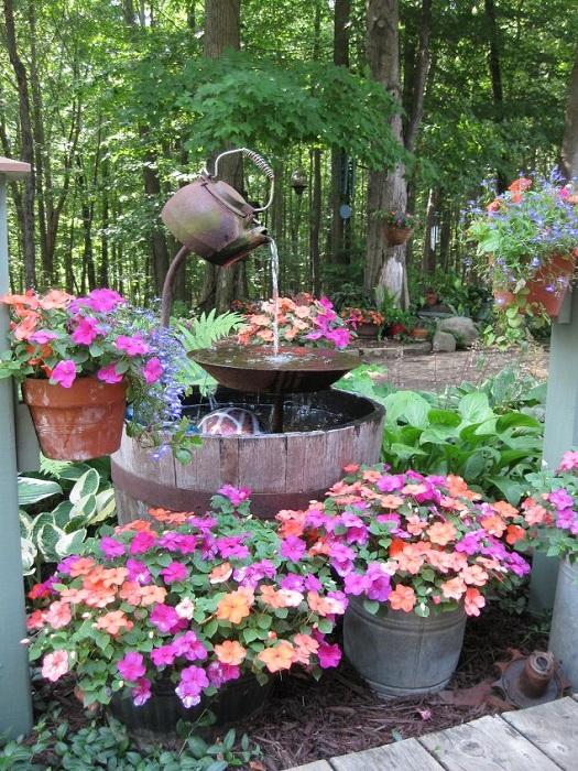 Причудливый фонтан в самом центре сада, добавит интересной атмосферы в оформление сада.