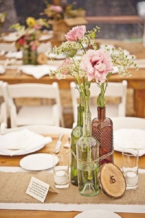 Бутылки можно использовать в виде ваз, то что создаст атмосферу легкости.