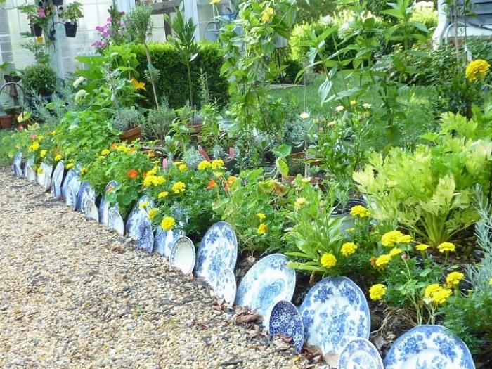 Крутой вариант оформления огорода, грядка огорожена от другой территории тарелками.