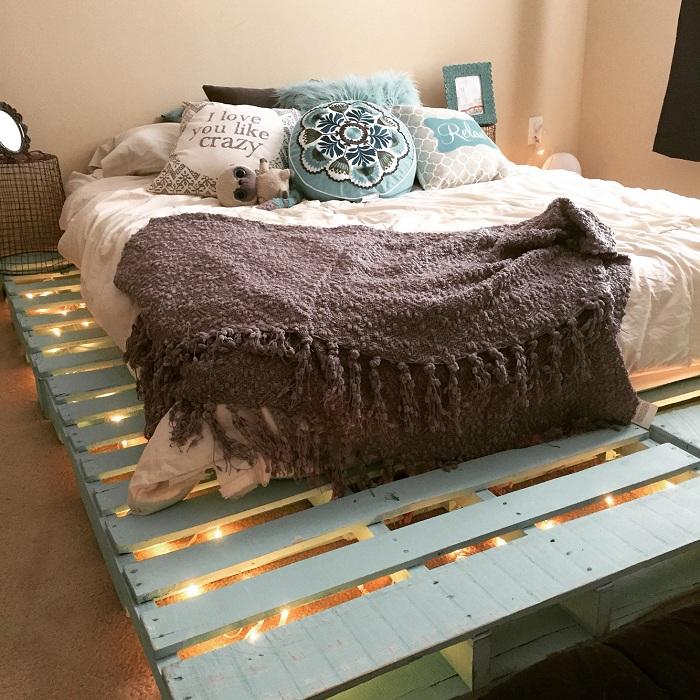 Хороший вариант оформления спальни с кроватью из паллет преображенной крутой подсветкой.