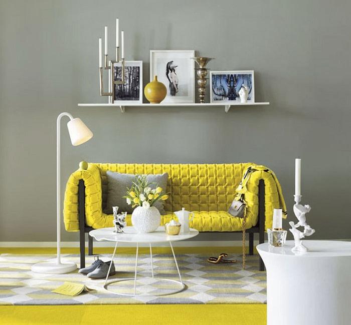 Красивое дизайнерское решение преобразить серую комнату при помощи желтого дивана.