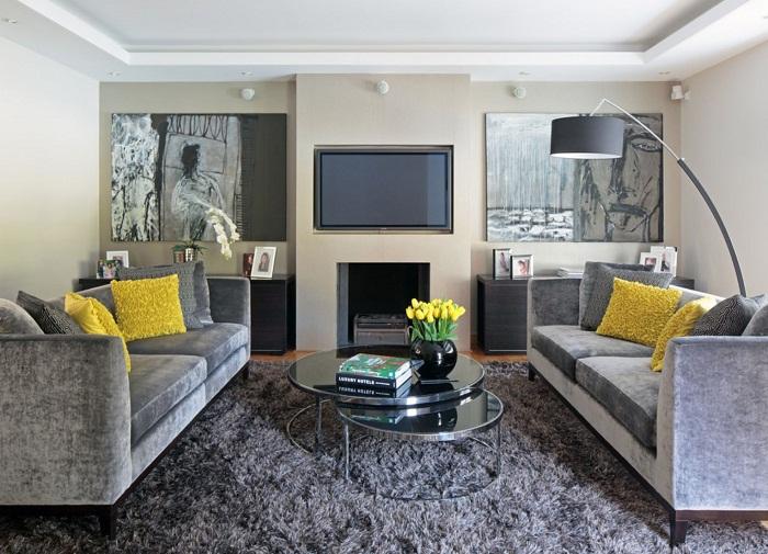 Преобразить гостиную в серых тонах возможно при помощи добавления желтых акцентов в неё, что создаст теплое настроение в ней.