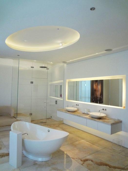 Ванная комната украшена скрытым освещением, добавляющим нотки шарма.