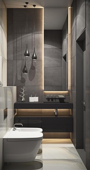 Оригинальный темный интерьер ванной комнаты преображен с помощью скрытого освещения.