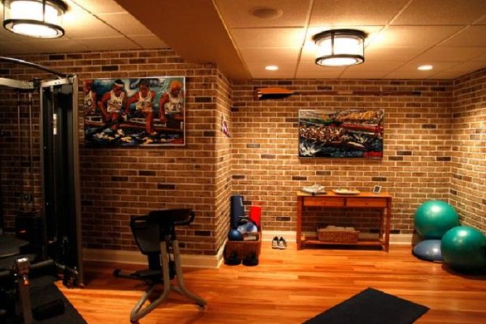 Интерьер спортивного зала в домашних условиях, который дополняет стена с каменной кладкой.