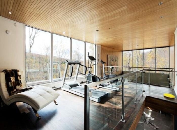 Домашний тренажерный зал с деревянным потолком и полом. Этот интерьер может вдохновить и очаровать.