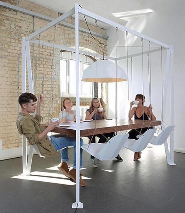 Необычное оформление обеденной зоны прекрасным столом и нестандартными качелями.