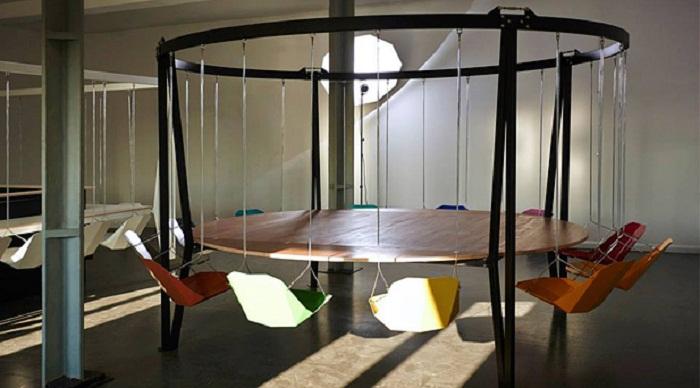 Красивое оформление круглого обеденного стола с нетипичными стульями вокруг.