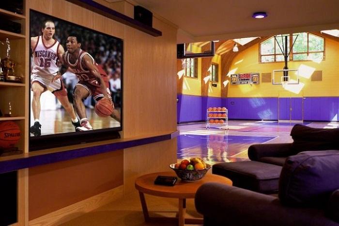 Уютная гостиная с большой плазмой дополнена баскетбольной площадкой, которая граничит с ней.