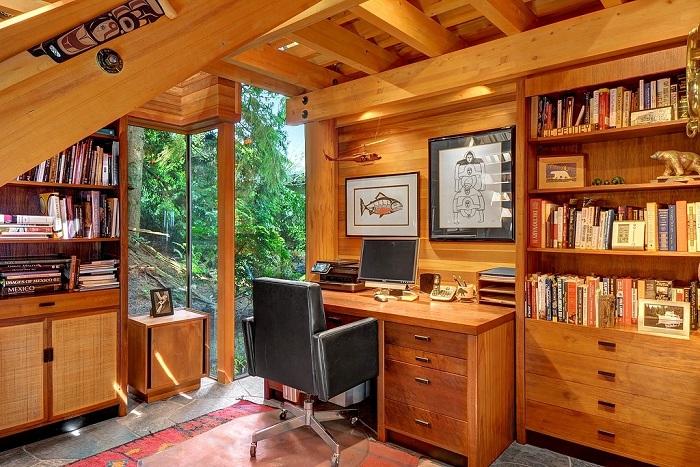 Интересный интерьер домашнего офиса в деревенском стиле украшает книжный шкаф.