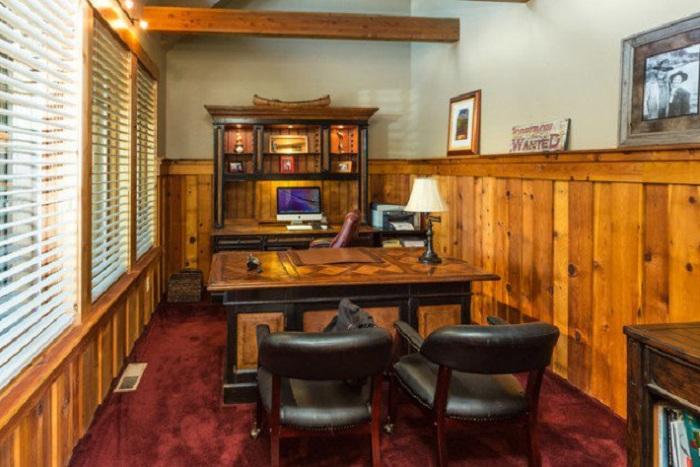 Небольшой офис в деревенском стиле под дерево с кожаными креслами.