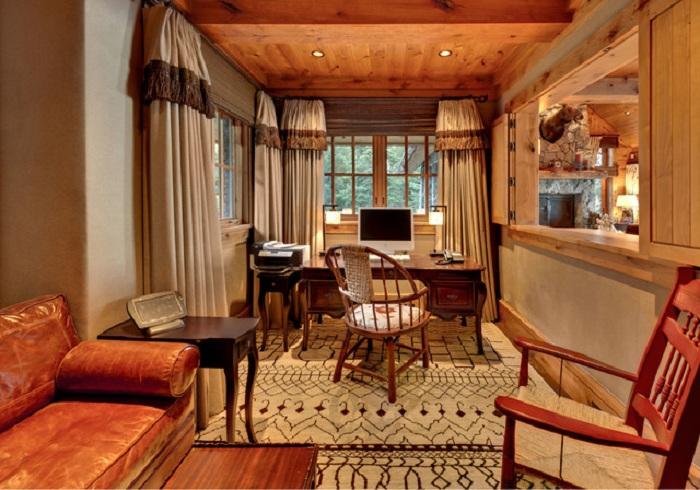 Симпатичный домашний офис с кожаным диваном и красивыми шторами.