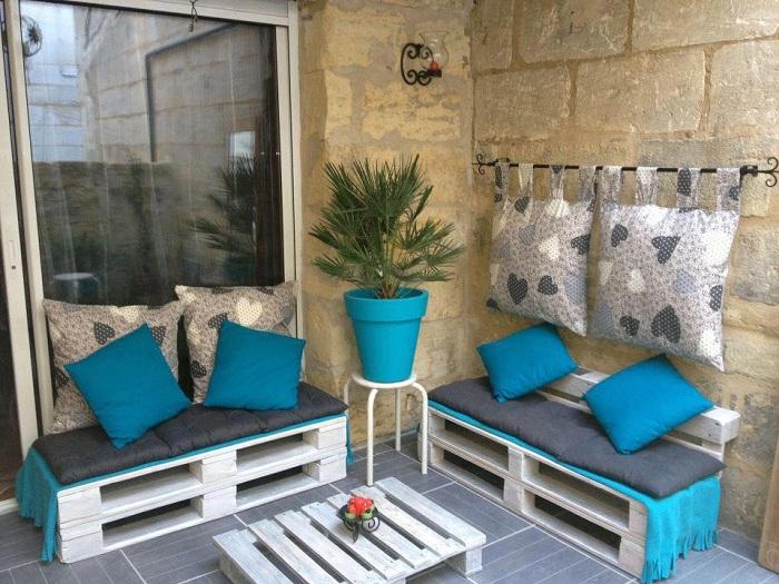 Интересные деревянные лавки, которые украшены яркими голубыми подушками.