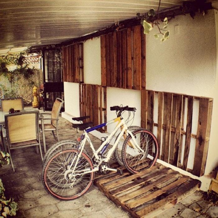 Возможно использовать деревянные поддоны в качестве велопарковки или же ими возможно украсить стены.