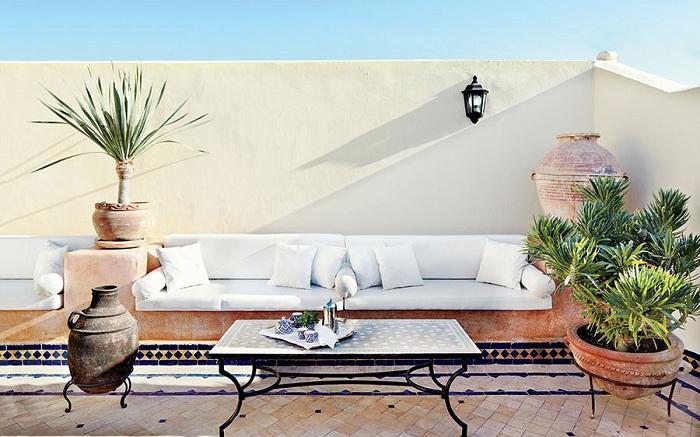 Отличным решением для дизайна зоны для отдыха на открытом воздухе станет простой, но симпатичный белый диван.