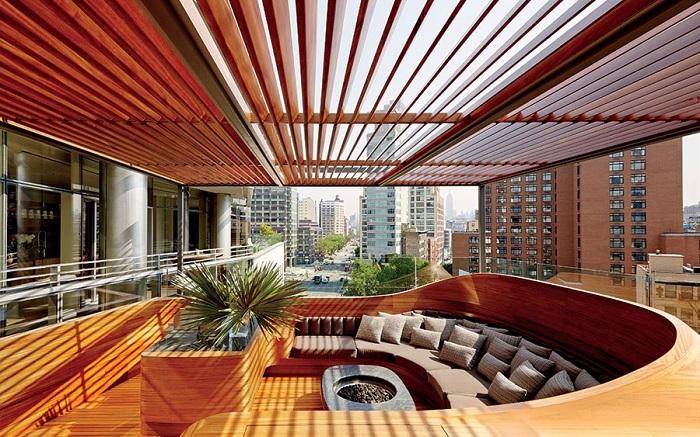 Интересный вариант оформить яркий диван с множеством подушек на открытом воздухе.