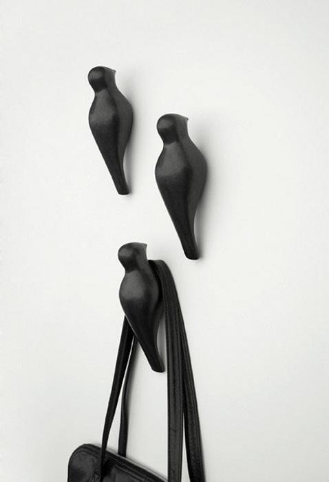 Интересные вешалки в форме птичек на стене - необычное решение для дома.