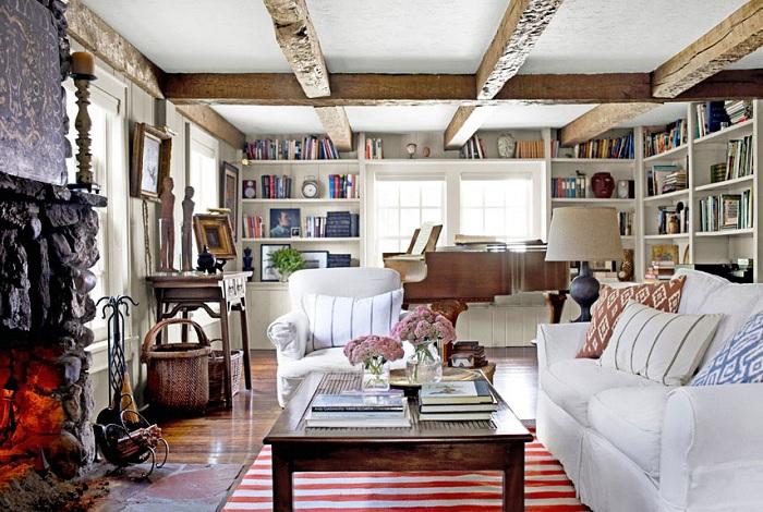 Симпатичный интерьер гостиной со светлой мебелью и деревянными балками.
