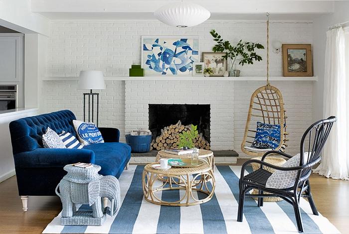 Гостиная с ультра-синим диваном и стенами, которые оформлены белой кирпичной кладкой.