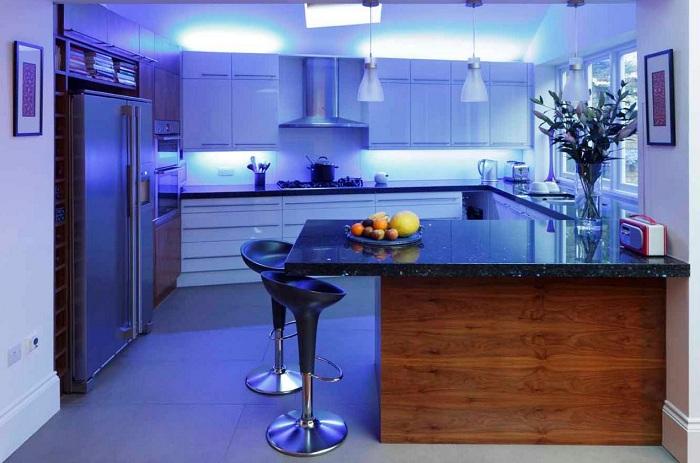 Современный интерьер кухни преображен с помощью голубой контрастной подсветки.