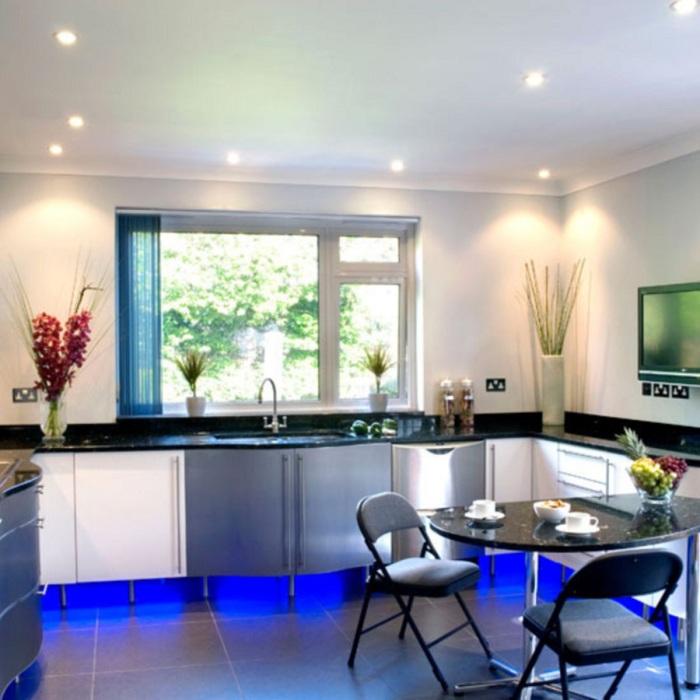 Яркий современный интерьер кухни благоустроен с помощью красивой подсветки.