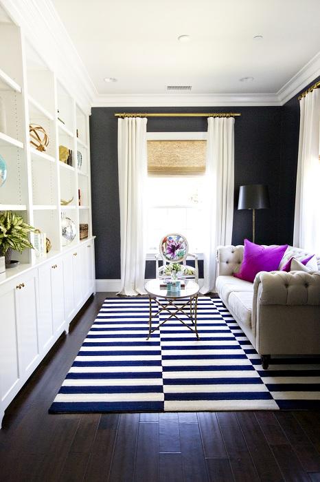 Хороший вариант расширить пространство гостиной с использованием полосатого черно-белого ковра.