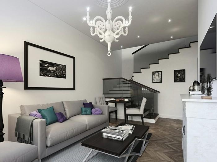 Оформлення вітальні в біло-сірих тонах розбавлене яскравими елементами декору.