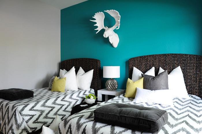 Комната для сна двоих с бирюзовой стеной смотрится стильно и симпатично.