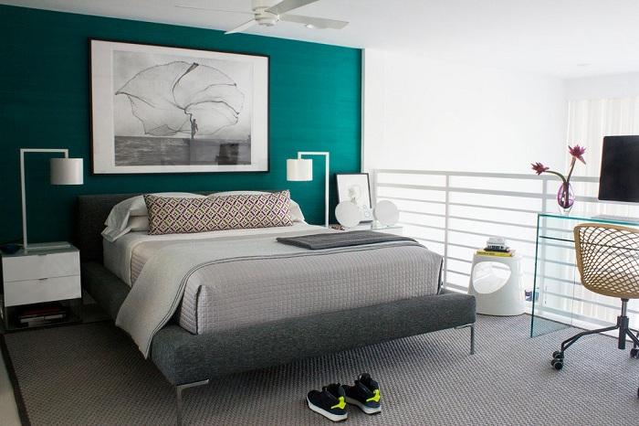 Симпатичная спальня с яркой бирюзовой стеной, которая дополняет общий интерьер.