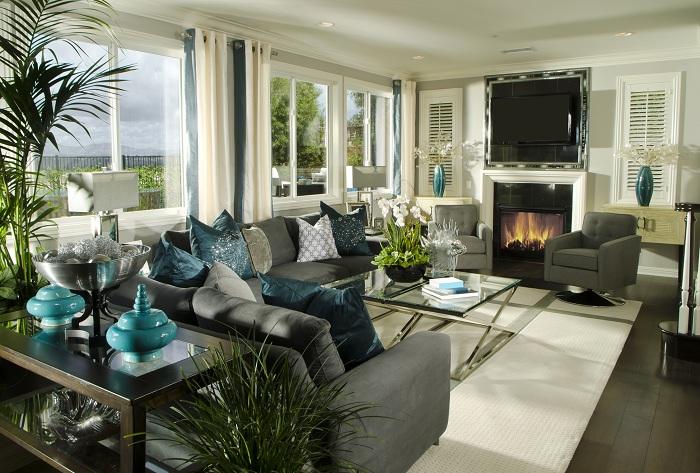 Интерьер гостиной оформлен в серо-бежевых цветах с бирюзовыми элементами декора.