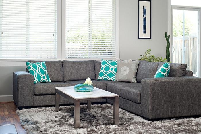 Симпатичный серый диван с интересными бирюзовыми подушками, которые украшают интерьер.