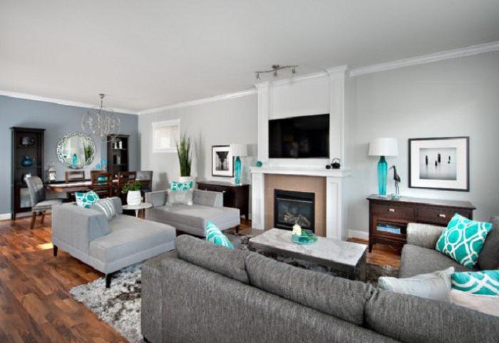 Пространство комнаты с серой мебелью и интересными бирюзовыми мотивами.