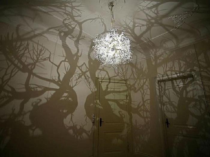 Интересное и очень крутое решение обустроить комнату с помощью люстры, которая превратит комнату в лес.