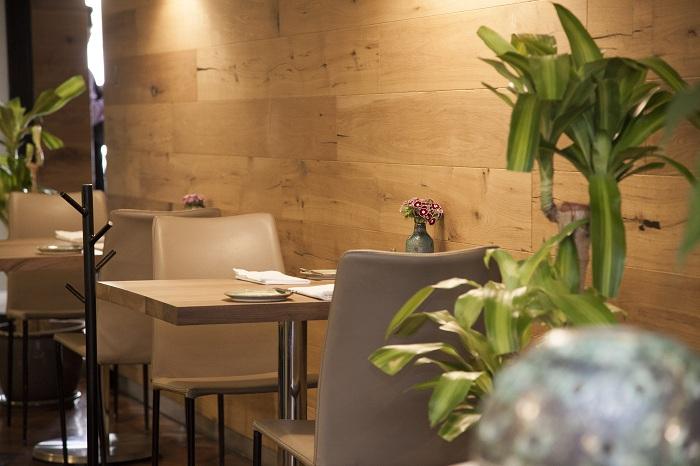 Расширенный открытый мир, присутствует в интерьерах Quintonil где вас окружат натуральные материалы, такие как дерево и зелень.