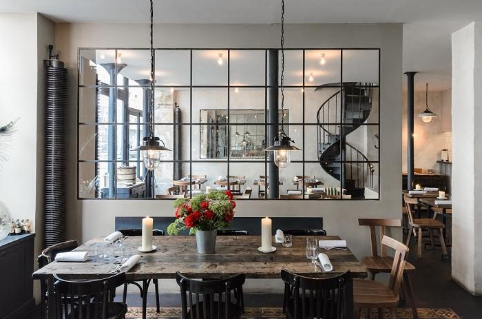 Эта французский ресторан в загородном стиле с промышленными деталями с перепрофилированной деревянной мебелью.