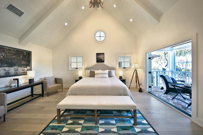 Отличный вариант оформления спальной под самим чердаком дома с нестандартной лампой-штативом - интересное решение.