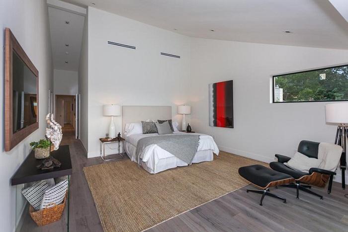 Очень практичный и интересный интерьер спальной в серых тонах, выглядит очень спокойно и дополнен лампой-штативом.